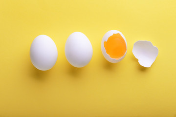 Cracked and whole chicken eggs on color background