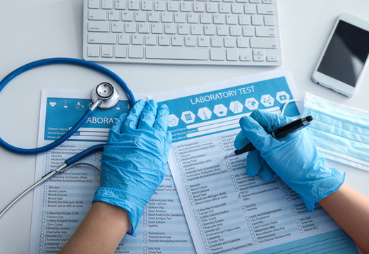 Female doctor filling in laboratory test request form on white table. Health care concept