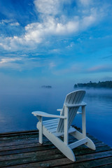 white deck chair on the dock, overlooking mist covered lake