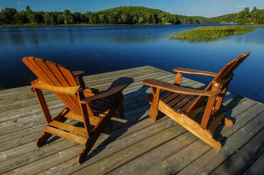 wooden Muskoka chairs on dock, overlooking deep blue lake