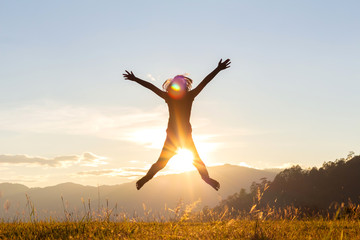 Silhouette of happy child jumping playing on mountain at sunset time