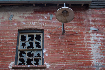 old window with broken glass panes on red brick wall