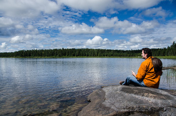 man sitting on rocks near a lake