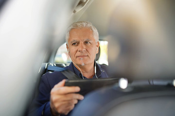 Passenger sitting in taxi back seat and using smartphone