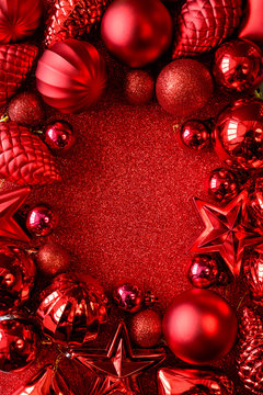Red Christmas frame. Christmas balls, stars, cones and hearts on red sparkles background. Flat lay. Top view. Copy space