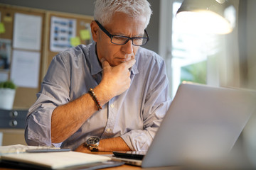 Mature man working in office