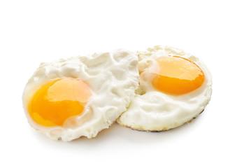 Fried tasty eggs with liquid yolk on white background