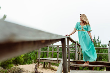 Beautiful blonde woman standing on a wooden walkway in the forest