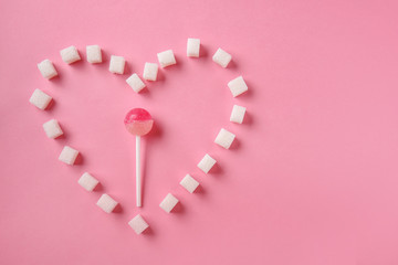 Creative composition made with white sugar cubes and lollipop on color background