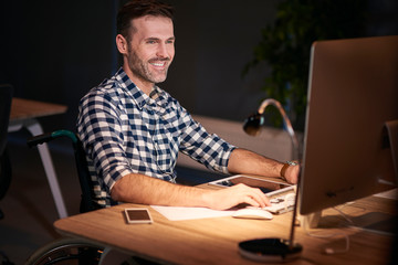 Disabled man working with technology in home office