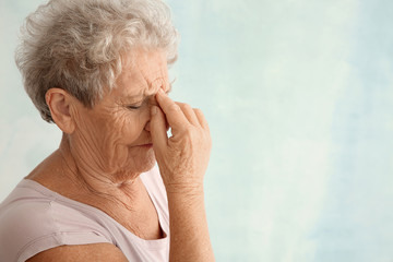 Senior woman suffering from headache on light background