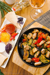 close up view of hot pan with roasted potatoes, vegetables and pork served on wooden board