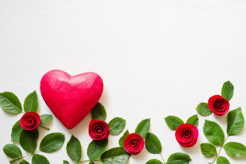 Red wooden heart, decorative roses on a white wooden background. A romantic background by St. Valentine's Day