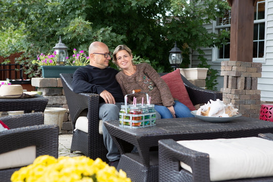 Adult couple sitting on couch at patio