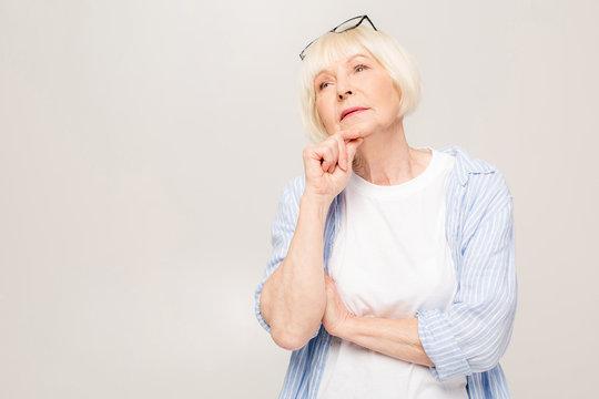 Portrait of thinking senior woman isolated over white background.