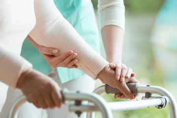Closeup of senior lady's hands holding a walker and helpful nurse supporting her