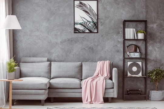 Pastel pink blanket on grey comfortable couch in contemporary living room with industrial black bookshelf