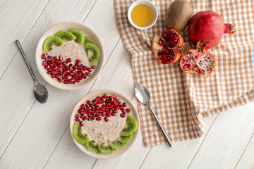 Plates with tasty oatmeal and fruits on white wooden table