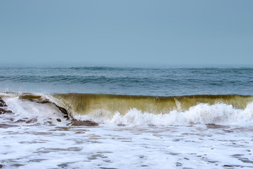 waves breaking on the shore with overcast sky