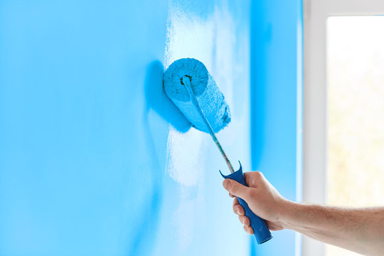 Male hand painting wall with paint roller. Painting apartment, renovating with blue color paint