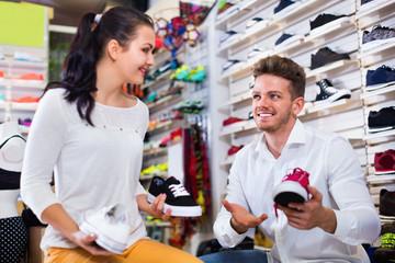 Man seller assisting girl in choosing sneakers