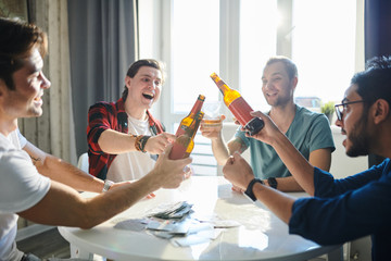 Happy young men sitting at the table and toasting with bottles of beer after good game in cards
