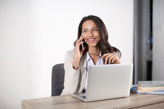 Young woman with laptop talking by mobile phone in office