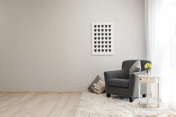 Interior of light room with cozy armchair near window
