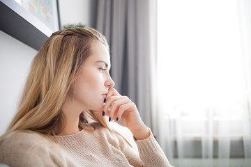 Alone sad woman thinking about something while sitting at home