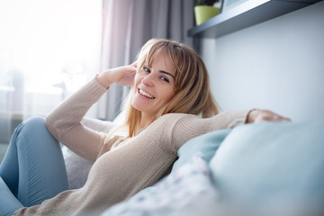 Cheerful smiling woman sitting on sofa at home looking friendly at camera, positive emotions