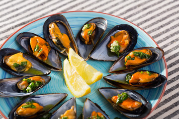 Steamed mussels with lemon on blue dish