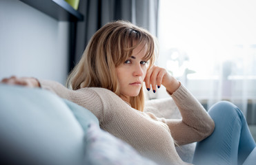 Depressed woman sitting on sofa at home looking sadly at camera, thinking about important things