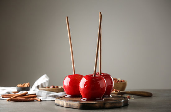 Wooden board with delicious candy apples on table