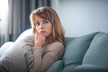 Depressed woman sitting on sofa at home, thinking about important things