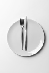 Plate with cutlery on white background
