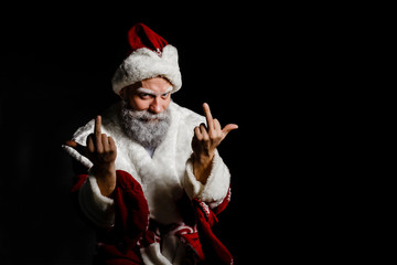 Portrait of a bad brutal mature Santa Claus showing middle finger signs, isolated on black background