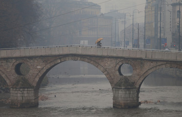 A man crosses a bridge as smog blankets Sarajevo