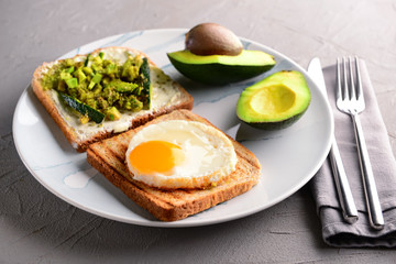 Plate with toasted bread, avocado and fried egg on grey table