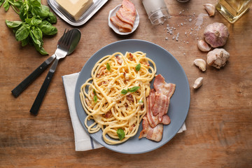 Plate with delicious spaghetti and bacon on wooden table, top view