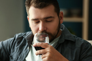 Man with glass of wine relaxing at home