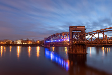 View of the illuminated old railway bridge Hubbrücke in Magdeburg, Germany.
