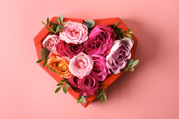 Composition with beautiful roses and heart shaped frame on color background