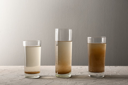 Glasses of dirty water on grey table