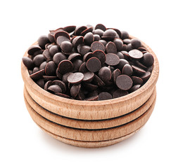 Wooden bowl with delicious dark chocolate chips on white background