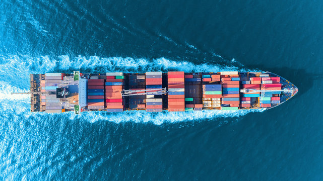 Aerial top view full speed container ship in the sea for logistics import export, shipping or transportation concept.
