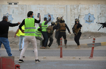 A demonstrator takes pictures of the Iraqi security forces detaining a protester during an anti-government protest near the government building in Basra