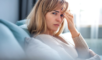 Sad woman sitting on sofa at home looking at camera, thinking about important things