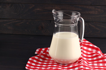 Milk in a jug on dark boards place for text copy space
