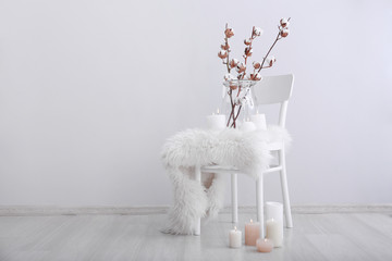 Chair with cotton flowers and burning candles near light wall