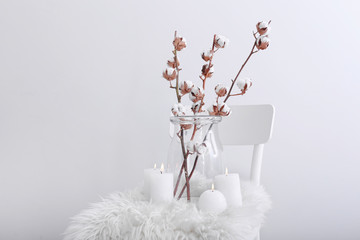 Cotton flowers and burning candles on chair against white background